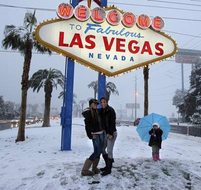 Snow falls at the Las Vegas sign and the people rejoice.